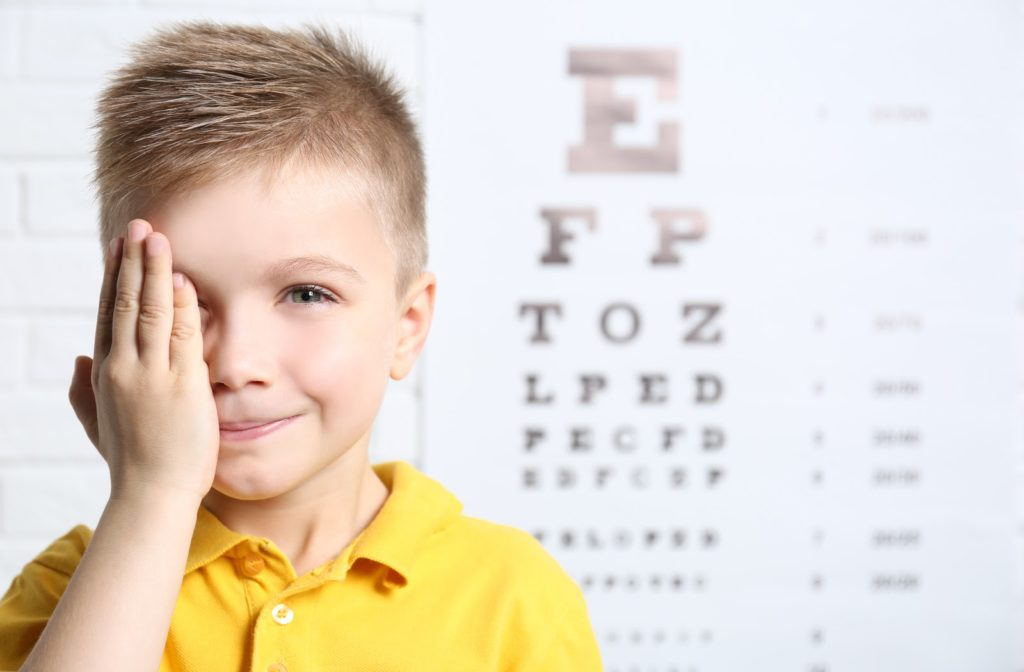 Child covering his right eye while he undergoes eye exam with reading chart in the background.